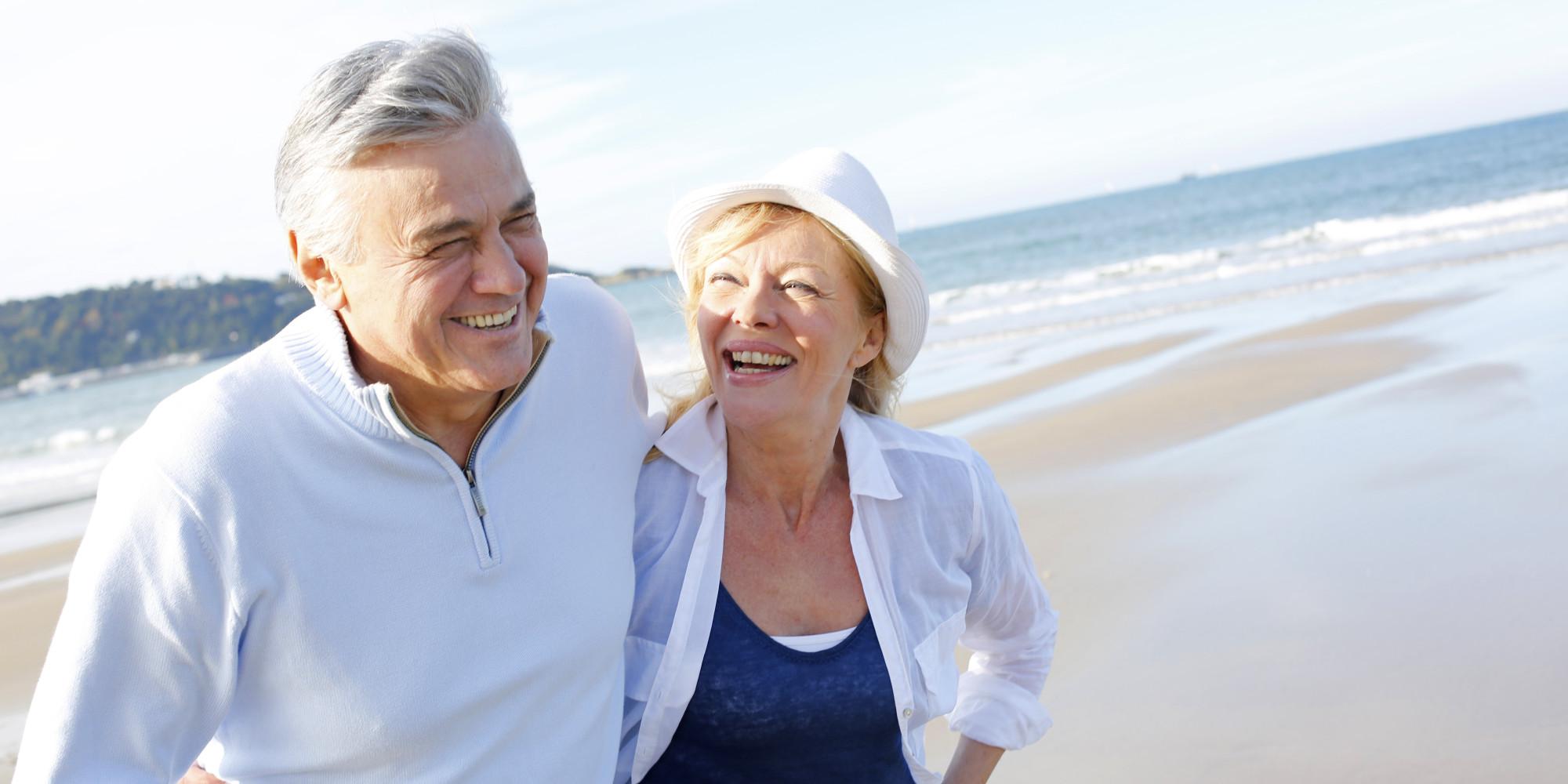 Happy senior couple walking on beach